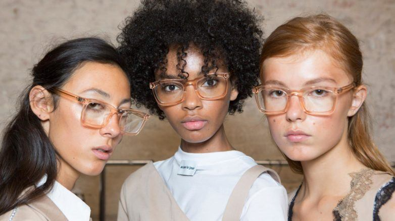 Anti-frizz spray: Models backstage with straight and natural curly hair in different lengths and colours all wearing glasses.