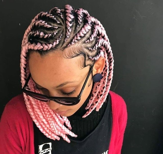 Dookie braids: Close up shot of a woman with pink dookie braided bob.
