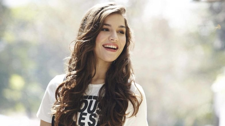 Brunette model laughing outside with heatless curls: