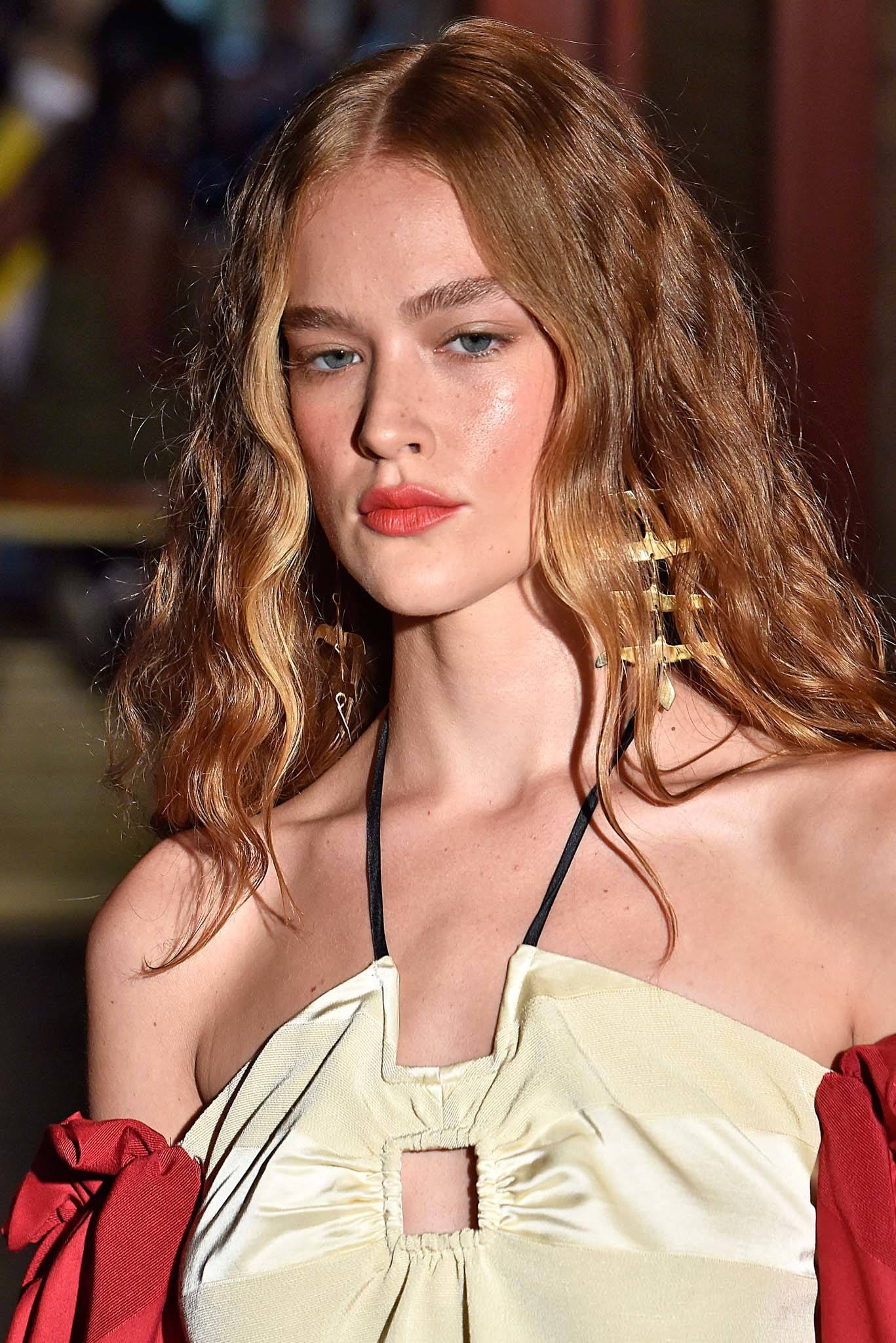NYFW SS19: Close up shot of a model with long bronde hair styled into wavy curls, wearing a halter neck dress and walking down the Hellessy runway