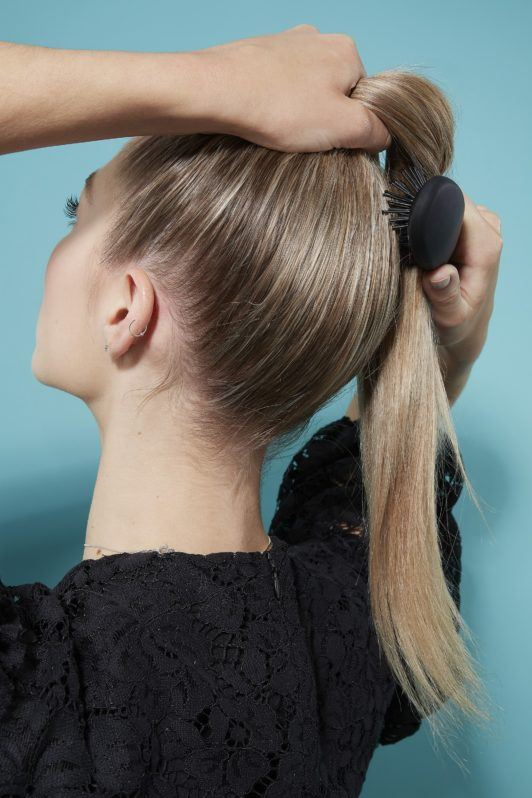 Blonde woman creating high ponytail