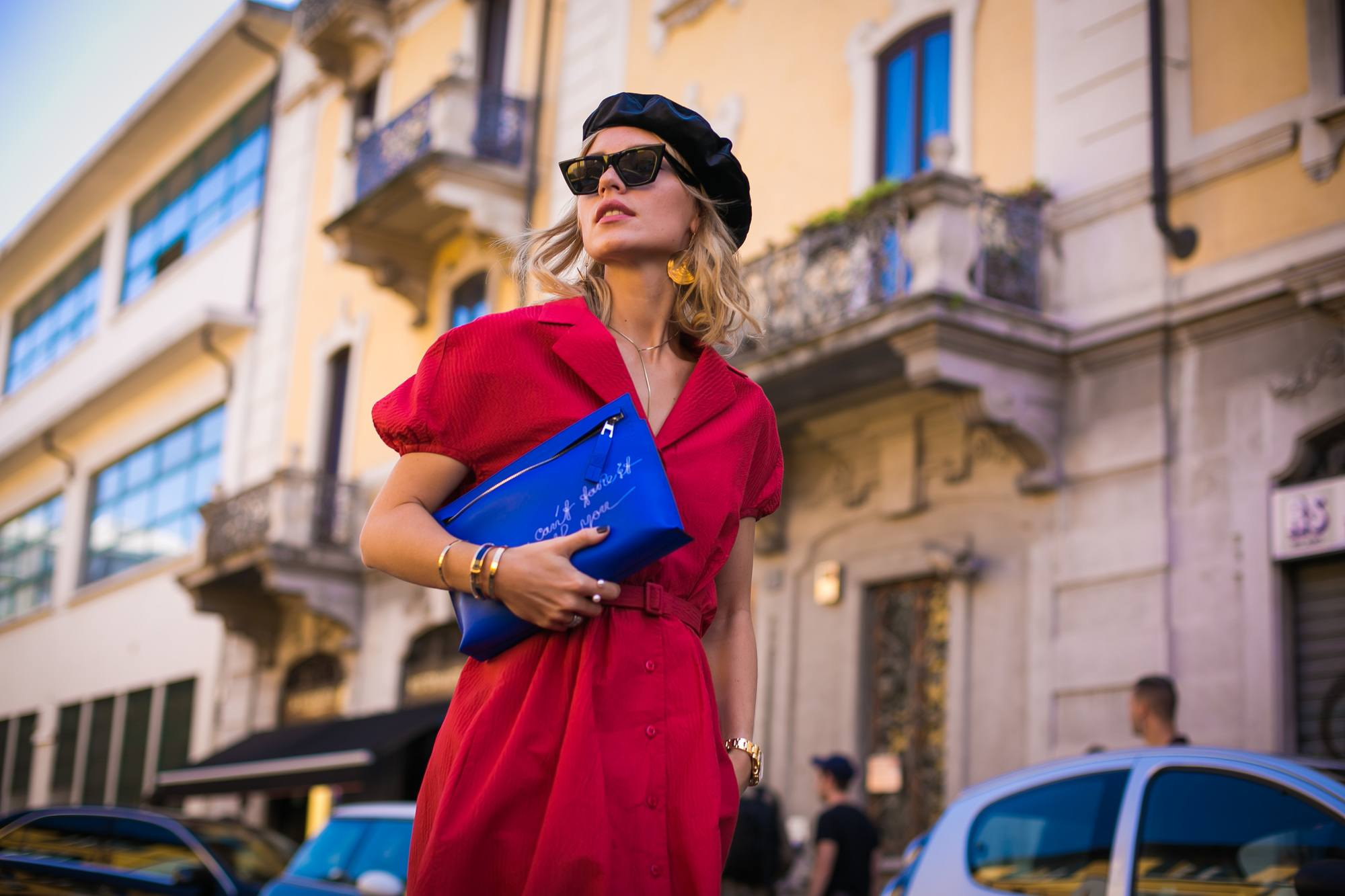 Milan Fashion Week Street Style FW19: Woman with short blonde shoulder length hair wearing a black beret, sunglasses and a red dress
