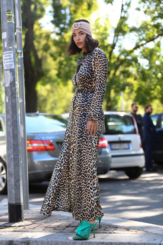 Milan Fashion Week Street Style FW19: Woman with shoulder length dark brown hair wearing a hair wrap and long pattern dress.