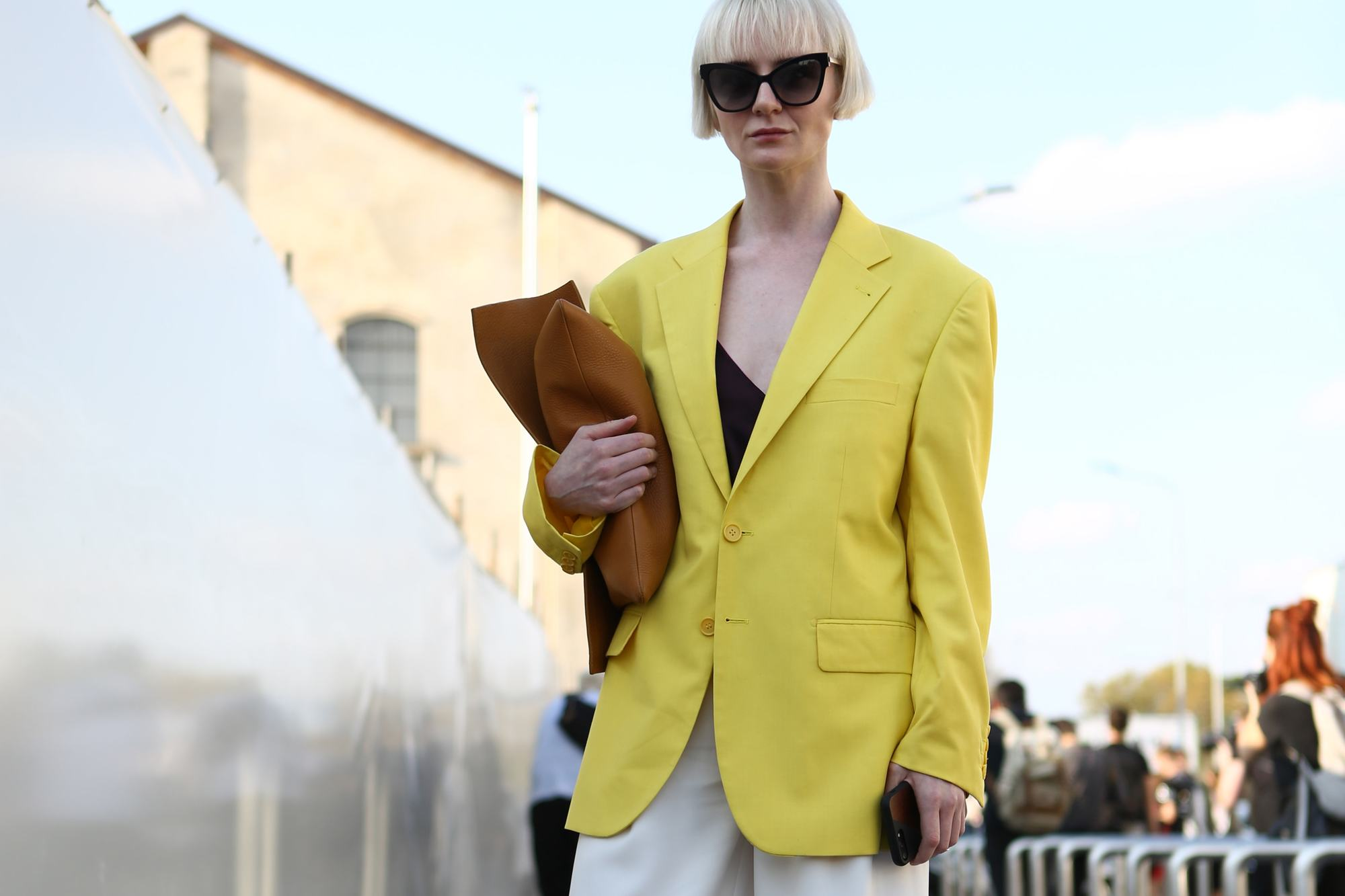 Milan Fashion Week Street Style FW19: Woman with short blonde bob with bangs wearing sunglasses and a yellow blazer.