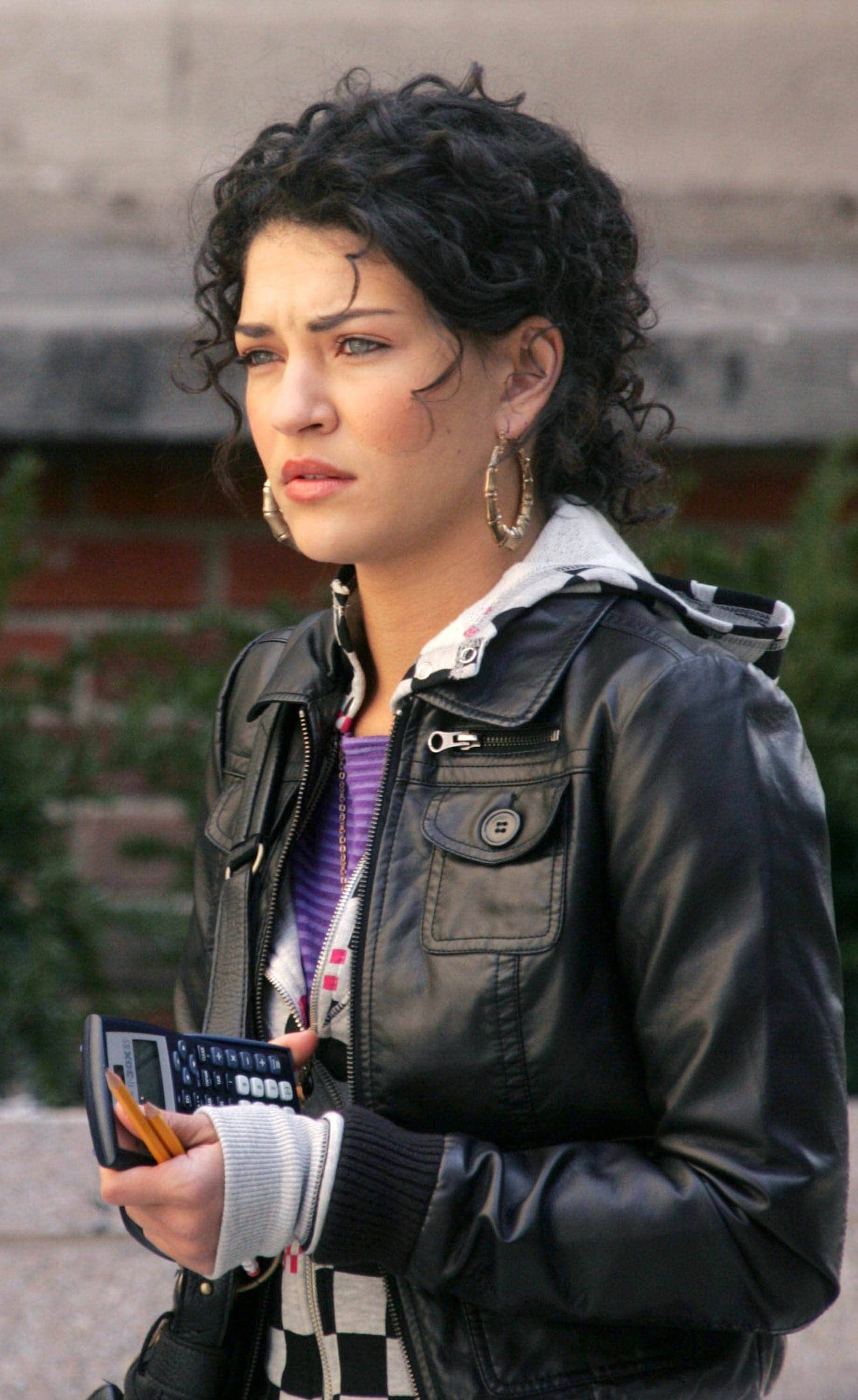 shot of jessica szhohr with curly hairstyle, leather jacket and jumper on the set of gossip girl