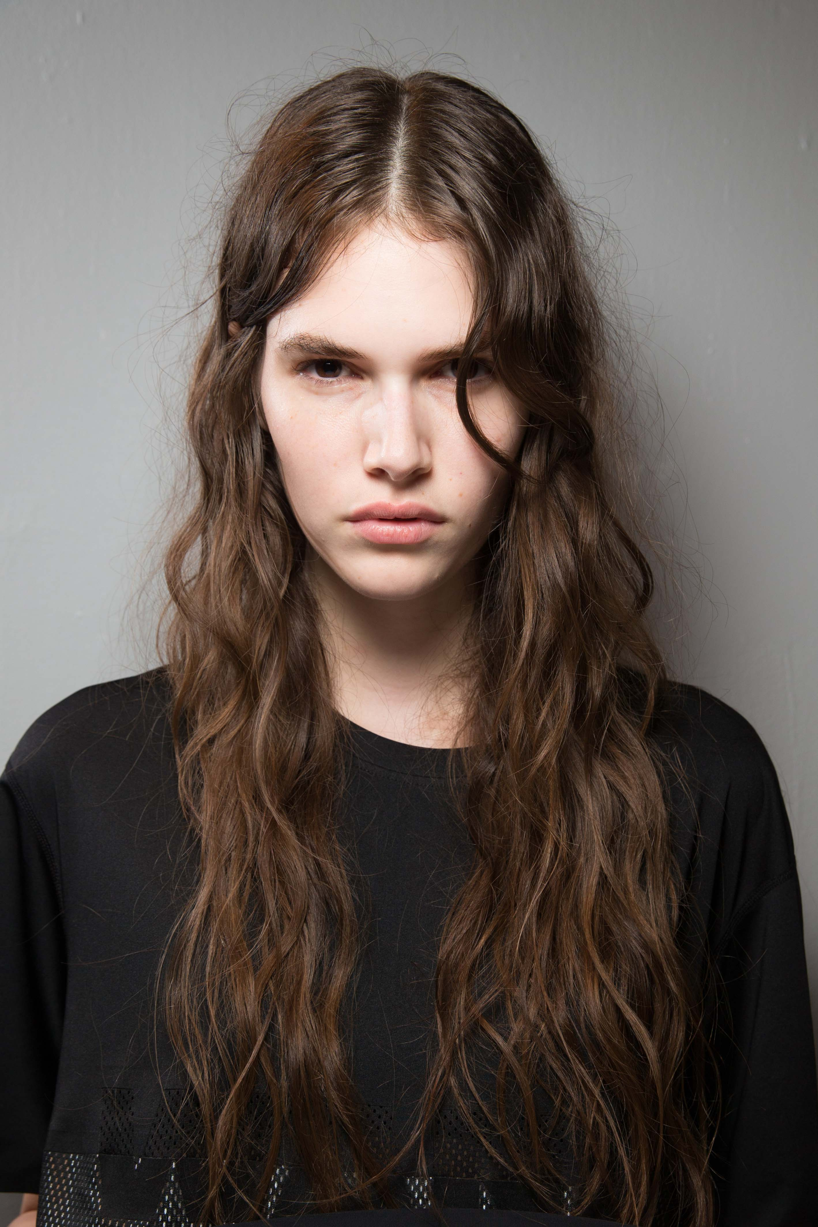 model with long brown hair and tight wavy hair