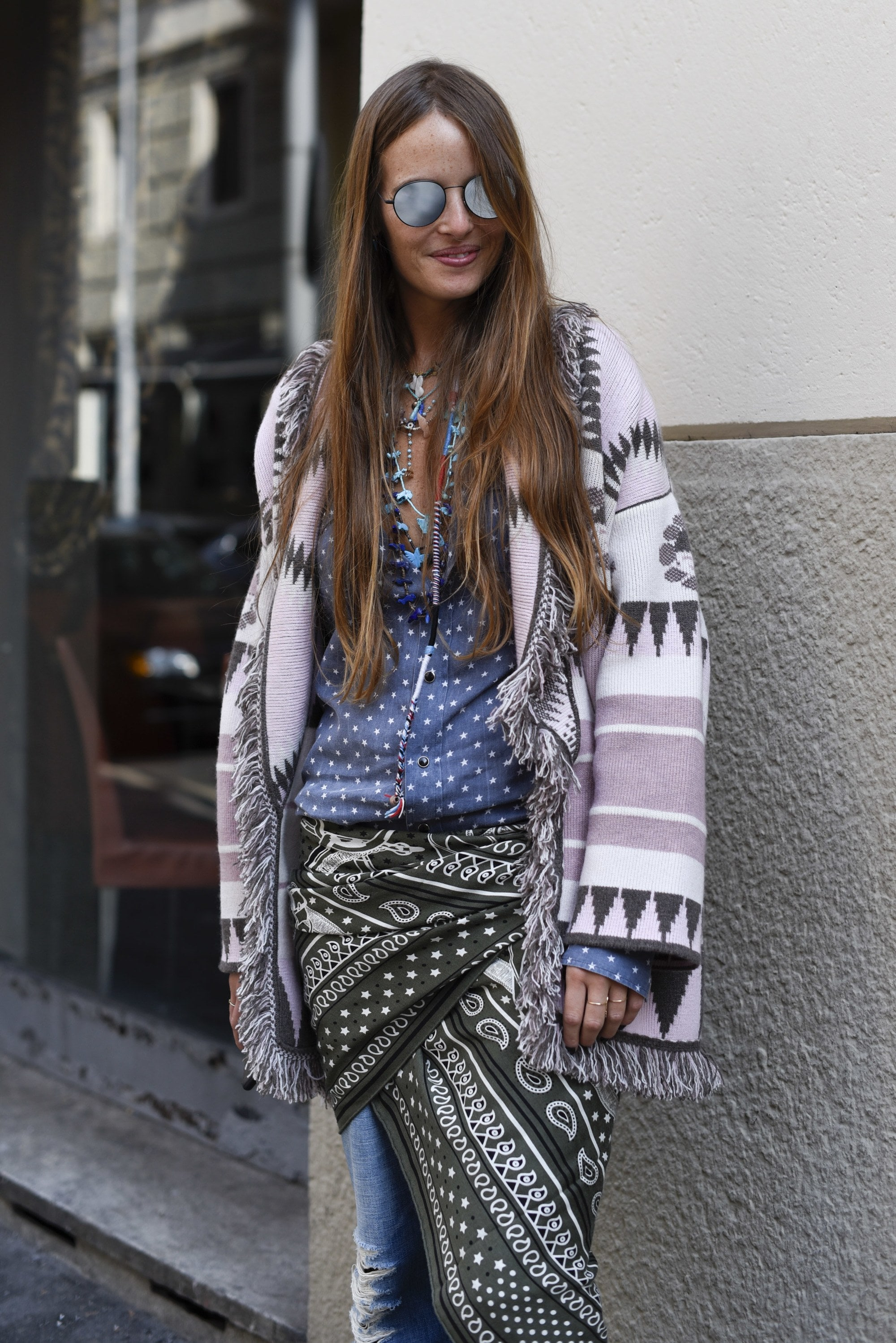 Milan Fashion Week Street Style FW19: Woman with long brunette hair wearing mirrored sunglasses and a bohemian outfit