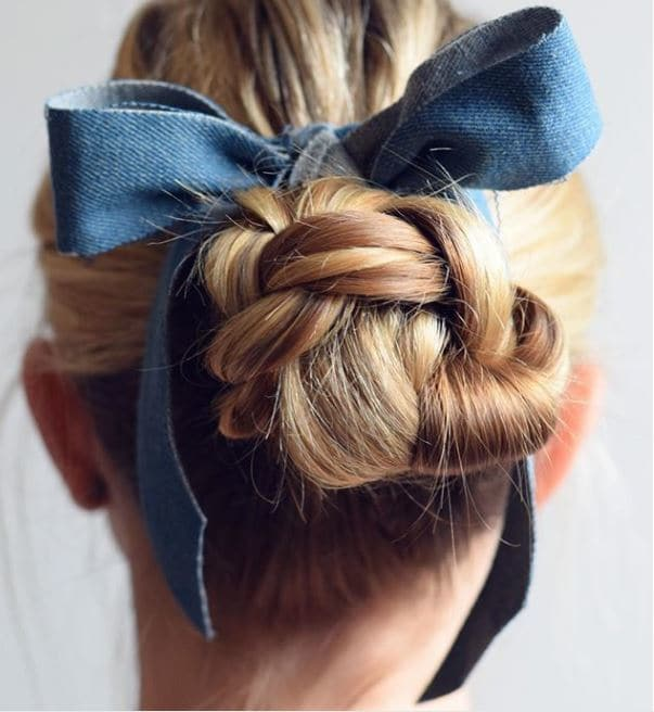 back view of blonde hair in low braided bun with ribbon wrapped around