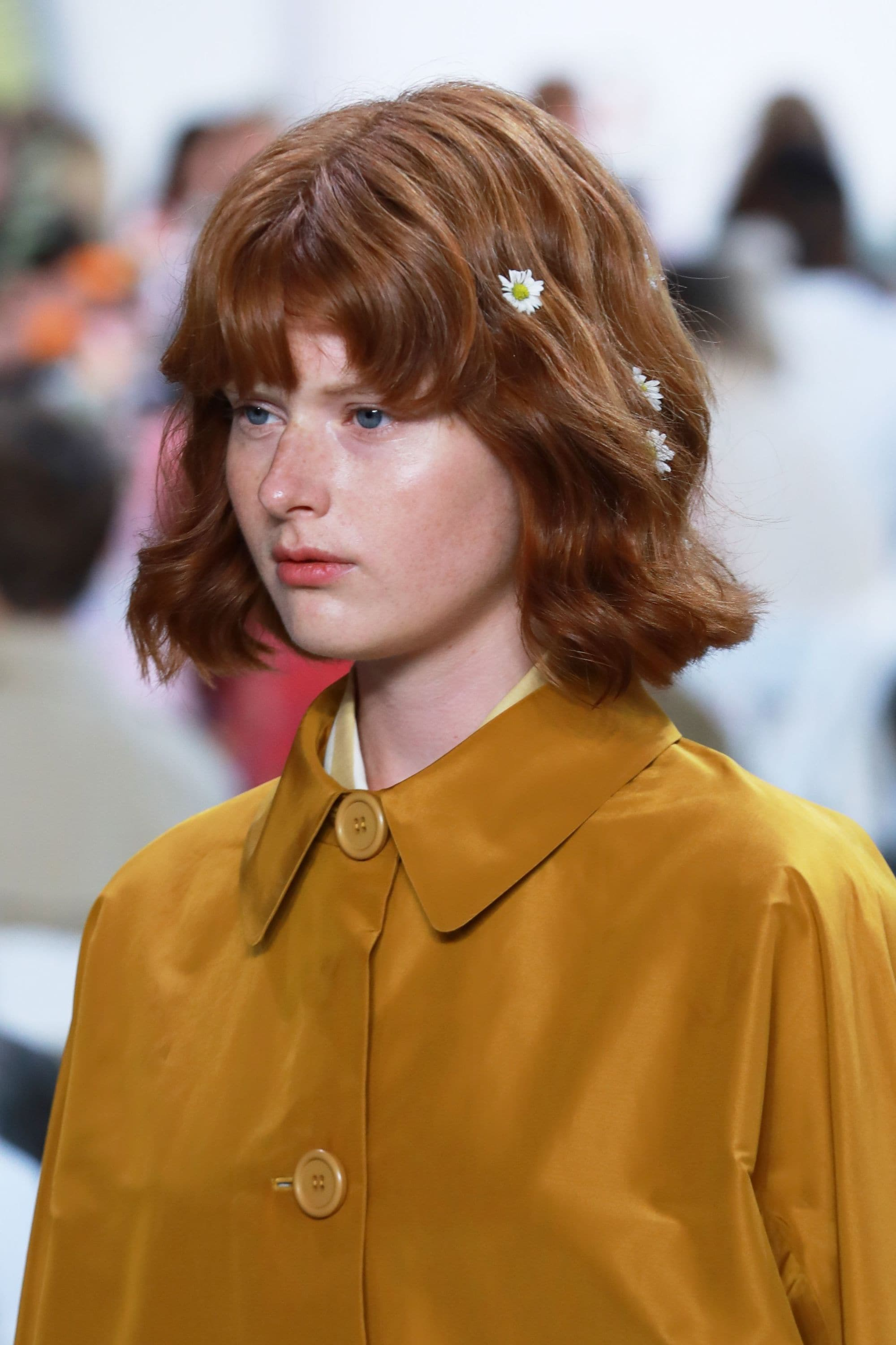 NYFW SS19: Close up shot of a model with dark red short wavy bob with fringe accessorised with daisy chain flowers