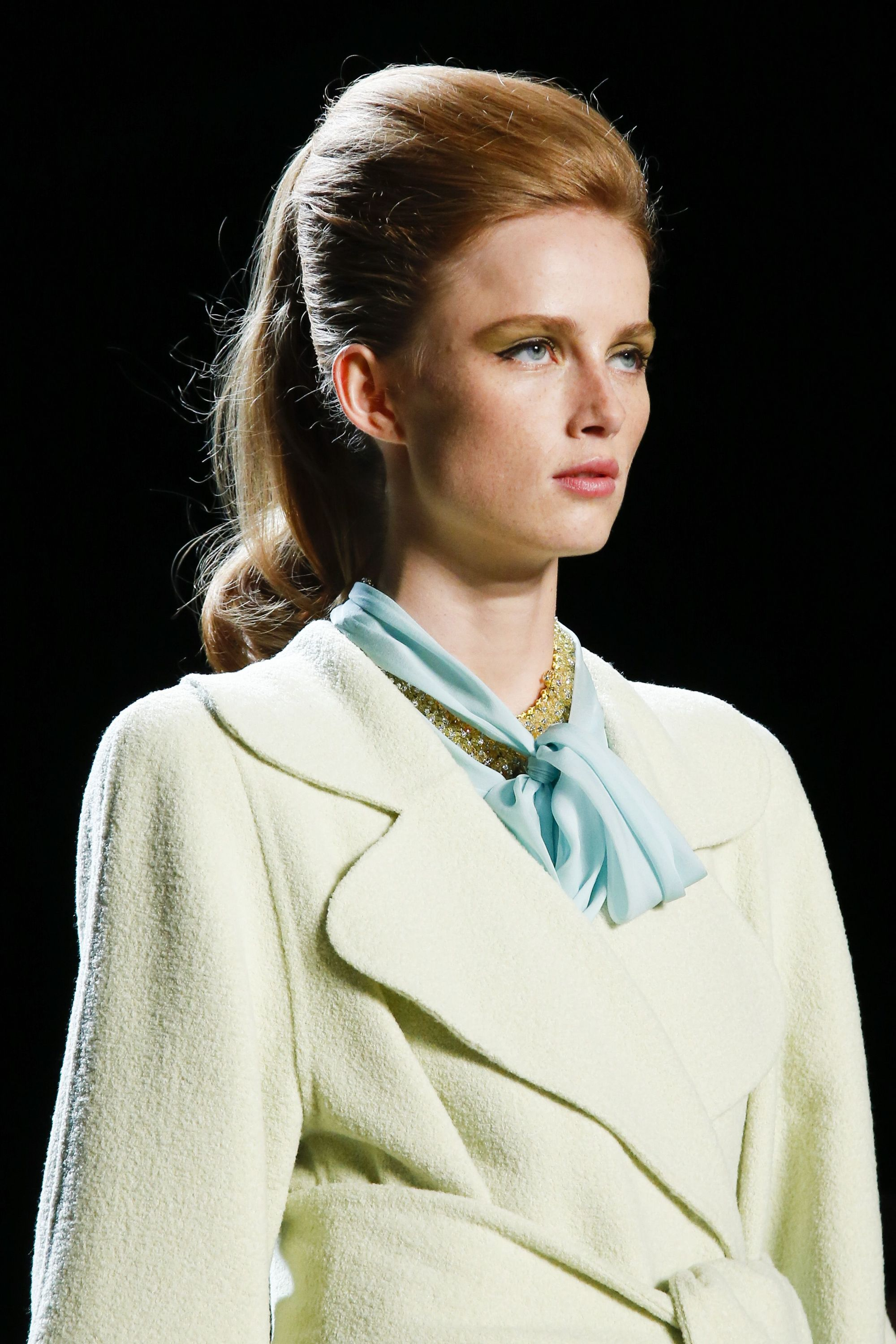 NYFW SS19: Close up shot of a model on the Marc Jacobs runway with dirty blonde long hair styled into a retro-inspired bouffant ponytail, wearing a jacket and a neckerchief