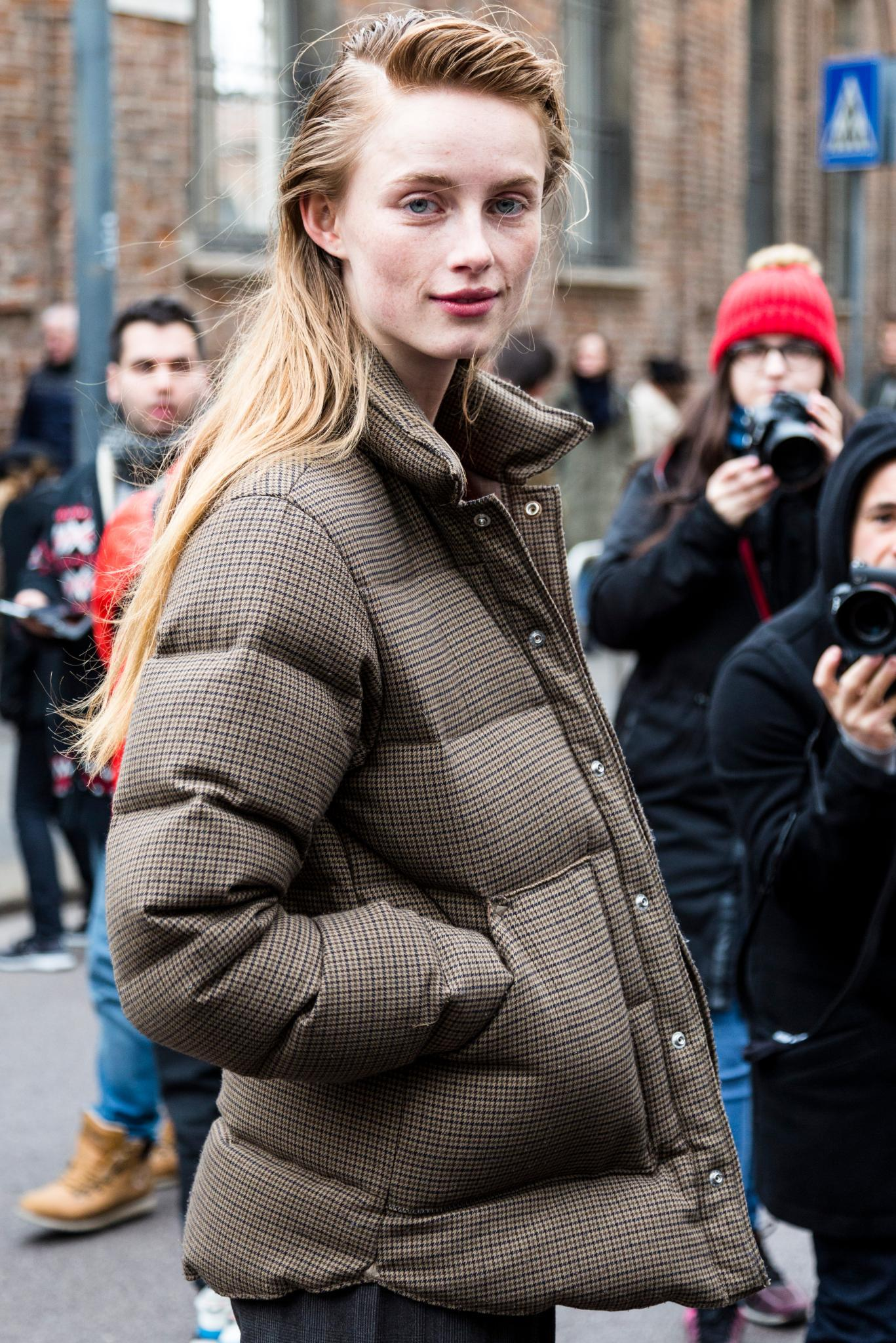 Milan Fashion Week Street Style: Woman with long blonde hair in side parting with soft quiff wearing a puffa jacket.