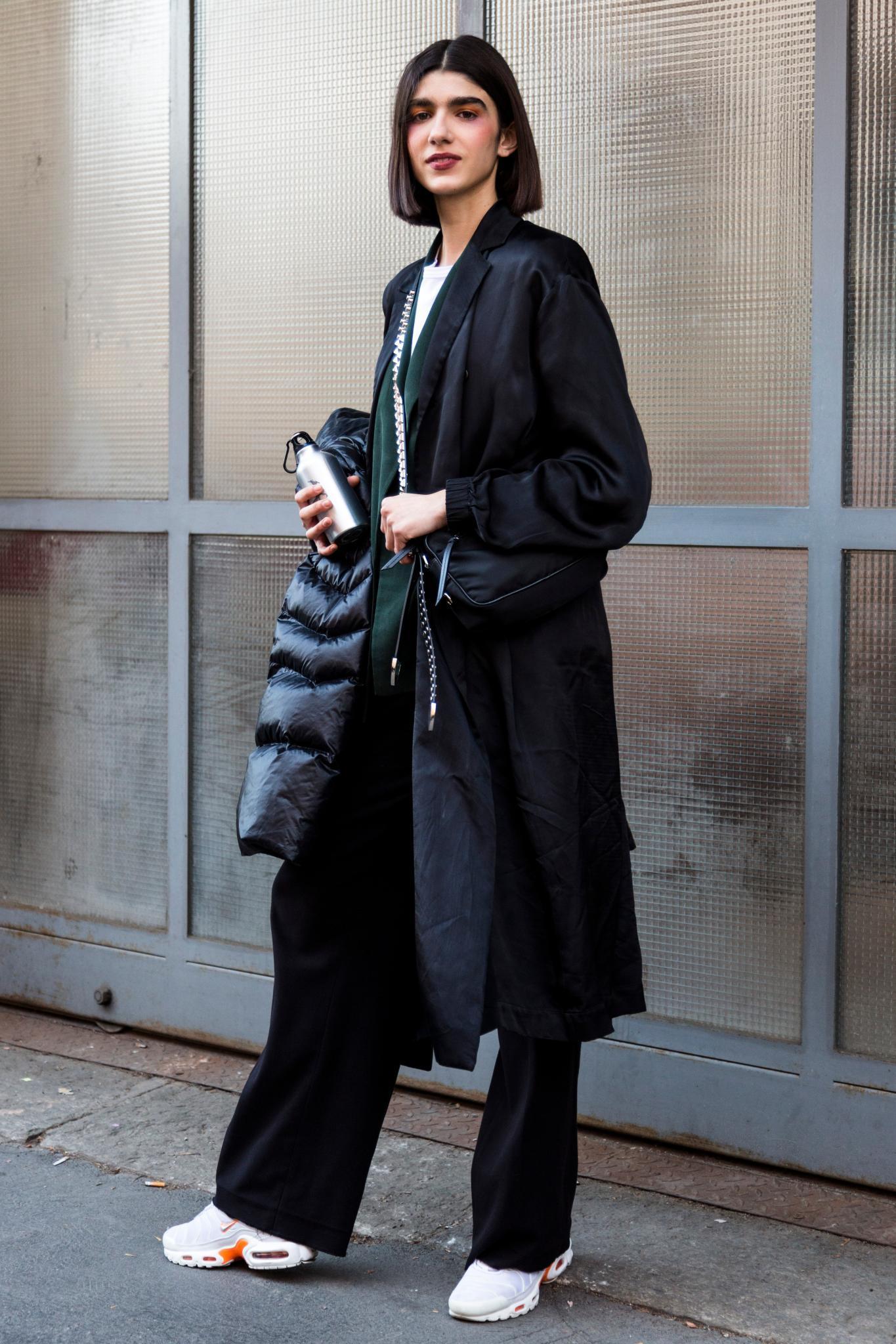 Milan Fashion Week Street Style: Woman with dark brown straight bob wearing black long coat.