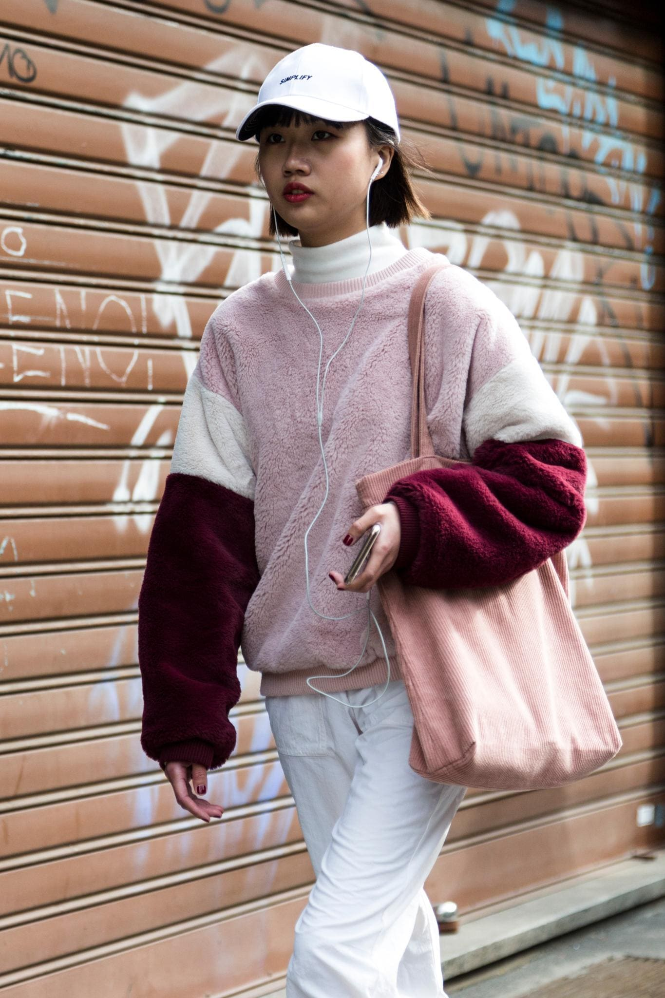 Milan Fashion Week Street Style: Woman with dark brown blunt bob wearing a white baseball cap and pink toned sports outfit.