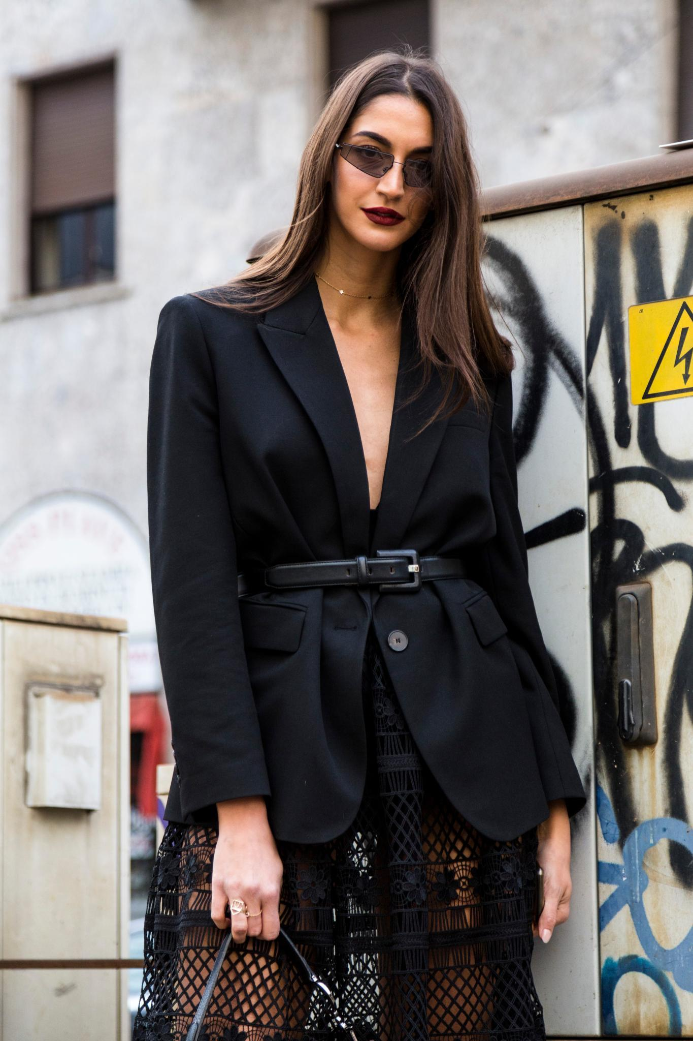 Milan Fashion Week Street Style: Woman with long straight sleek brown hair with long layers wearing black blazer with belt.