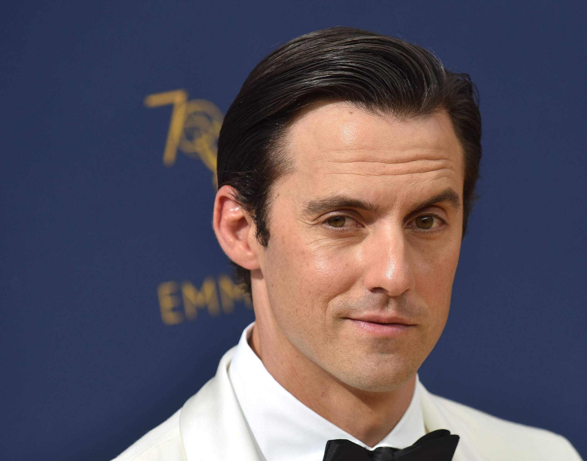 Gilmore Girls and This Is Us actor Milo Ventimiglia at the Emmy Awards 2018 with slick gelled hair wearing a white suit and black bow tie