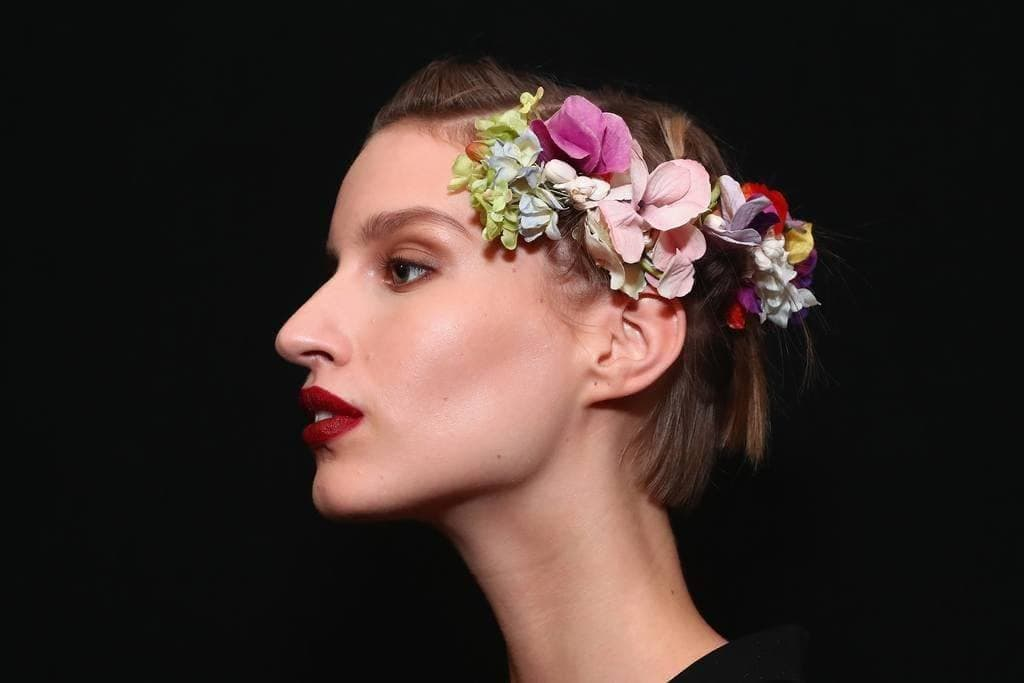 woman backstage at the naeem khan ss18 show with flowers in her short blonde hair