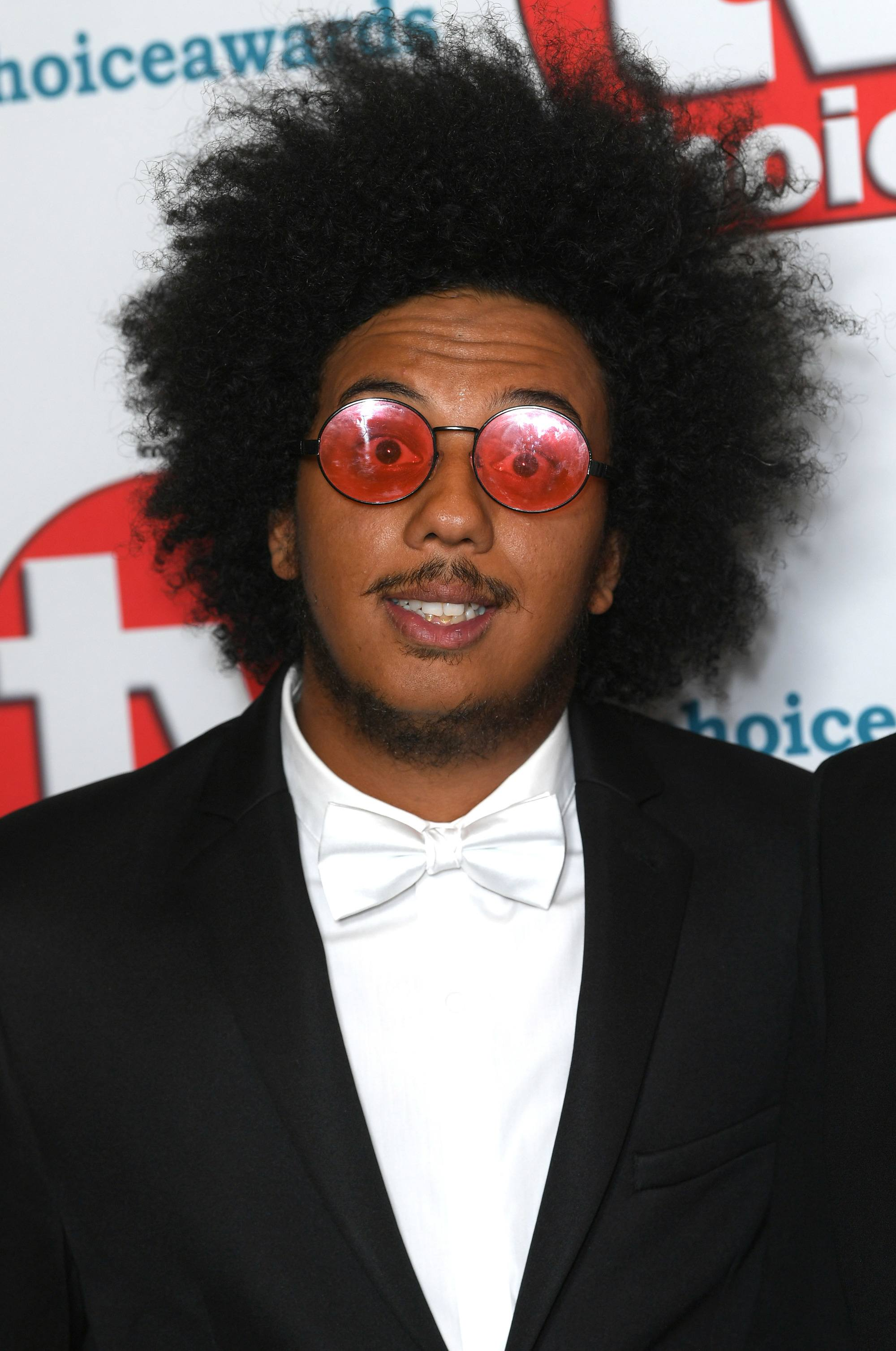 TV Choice Awards: Close up shot of Nathan Byron with medium dark brown natural afro hairstyle, wearing red sunglasses and white tuxedo and black jacket on the red carpet