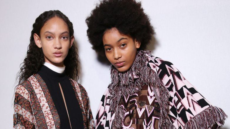 Natural hair textures: Two models backstage with curly hair, one with long spiral curls, the other with a tightly coiled afro