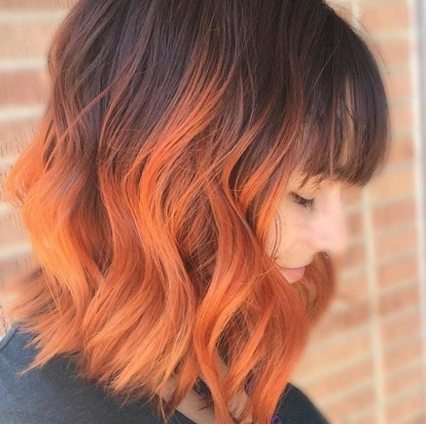 Pumpkin spice hair: Close up shot of a woman with dark brown long bob with pumpkin spice ends, posing outside