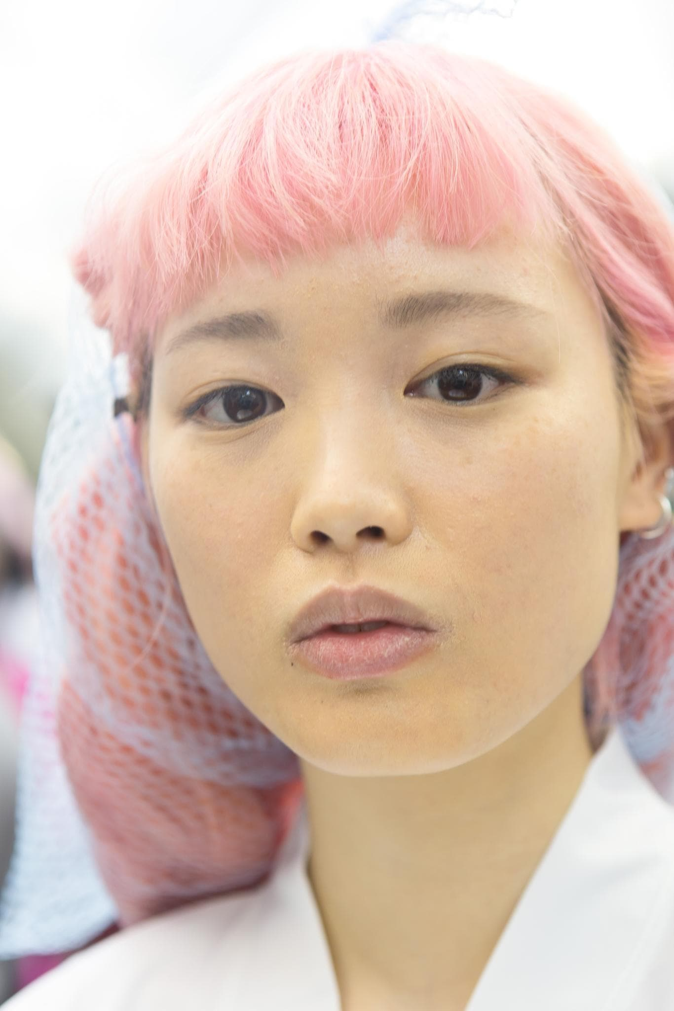 close up shot of model with pink hair in net backstage at a show
