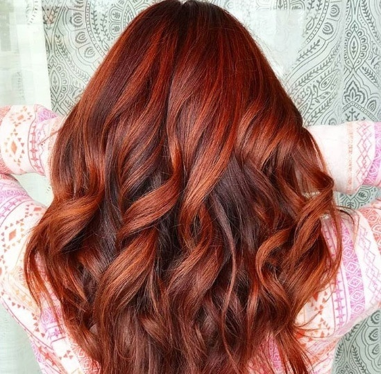 Pumpkin spice hair: Close up shot of a woman with dark pumpkin red hair with brown base, styled into loose curls