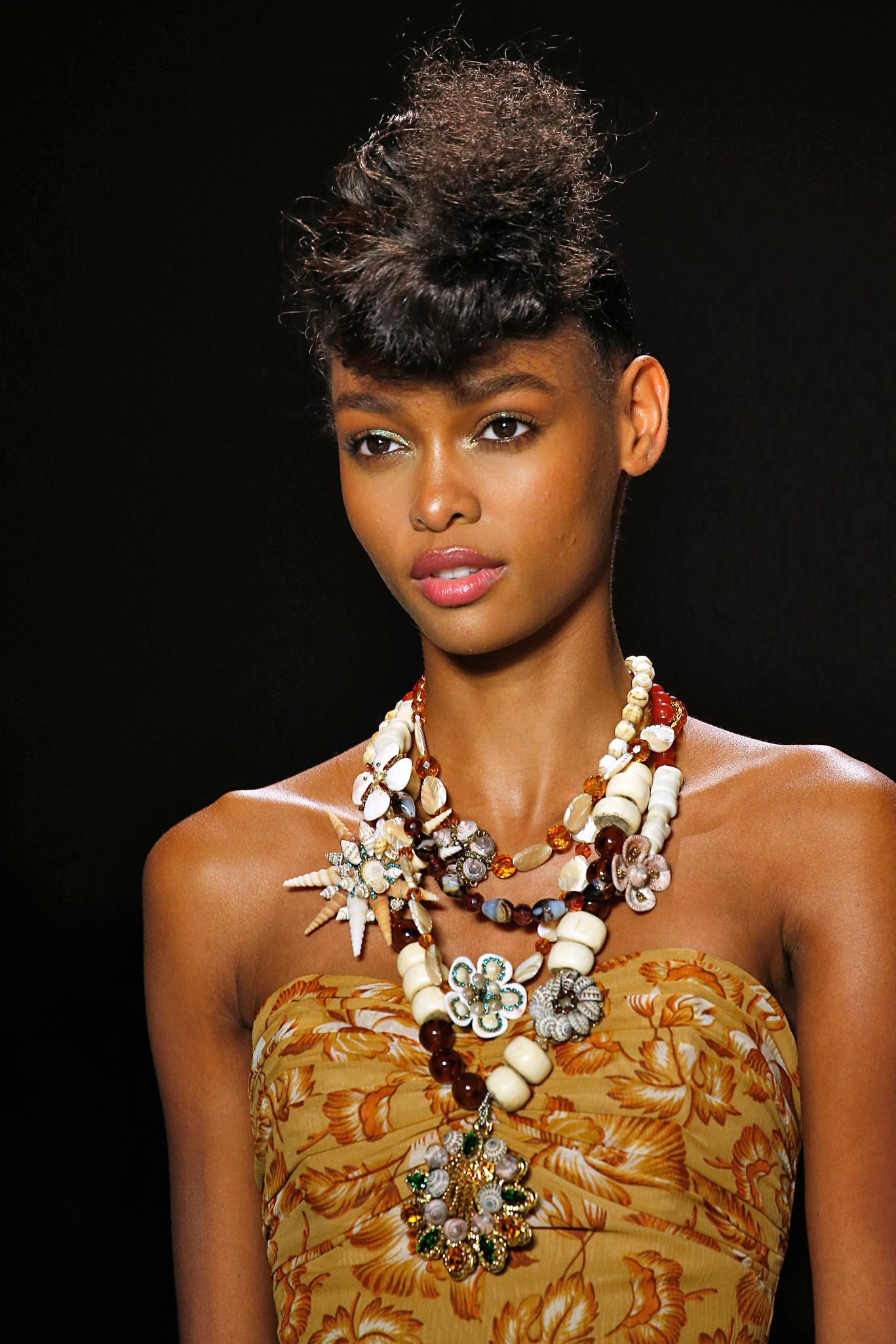 NYFW SS19: Close up shot of a model with dark brown relaxed hair styled into a '50s-inspired retro updo, wearing beaded necklaces and brown sweetheart dress on the Anna Sui runway