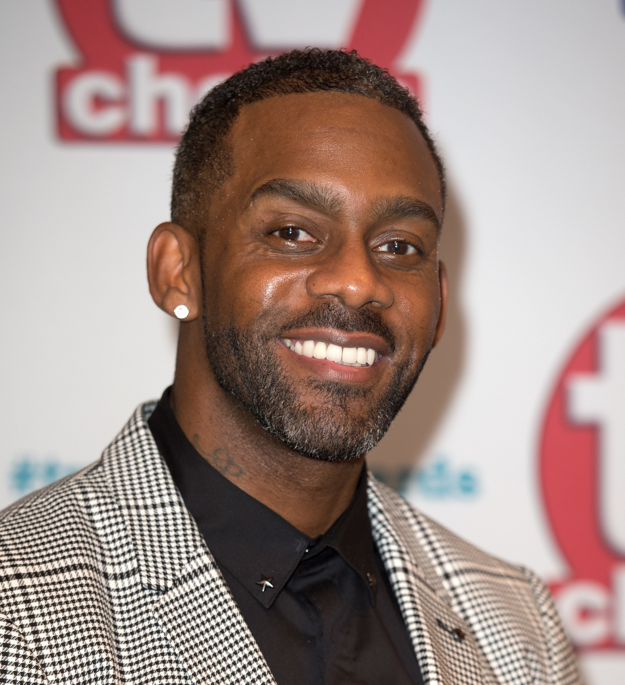 close up shot of richard blackwood with high top low fade haircut wearing smart outfit on the red carpet