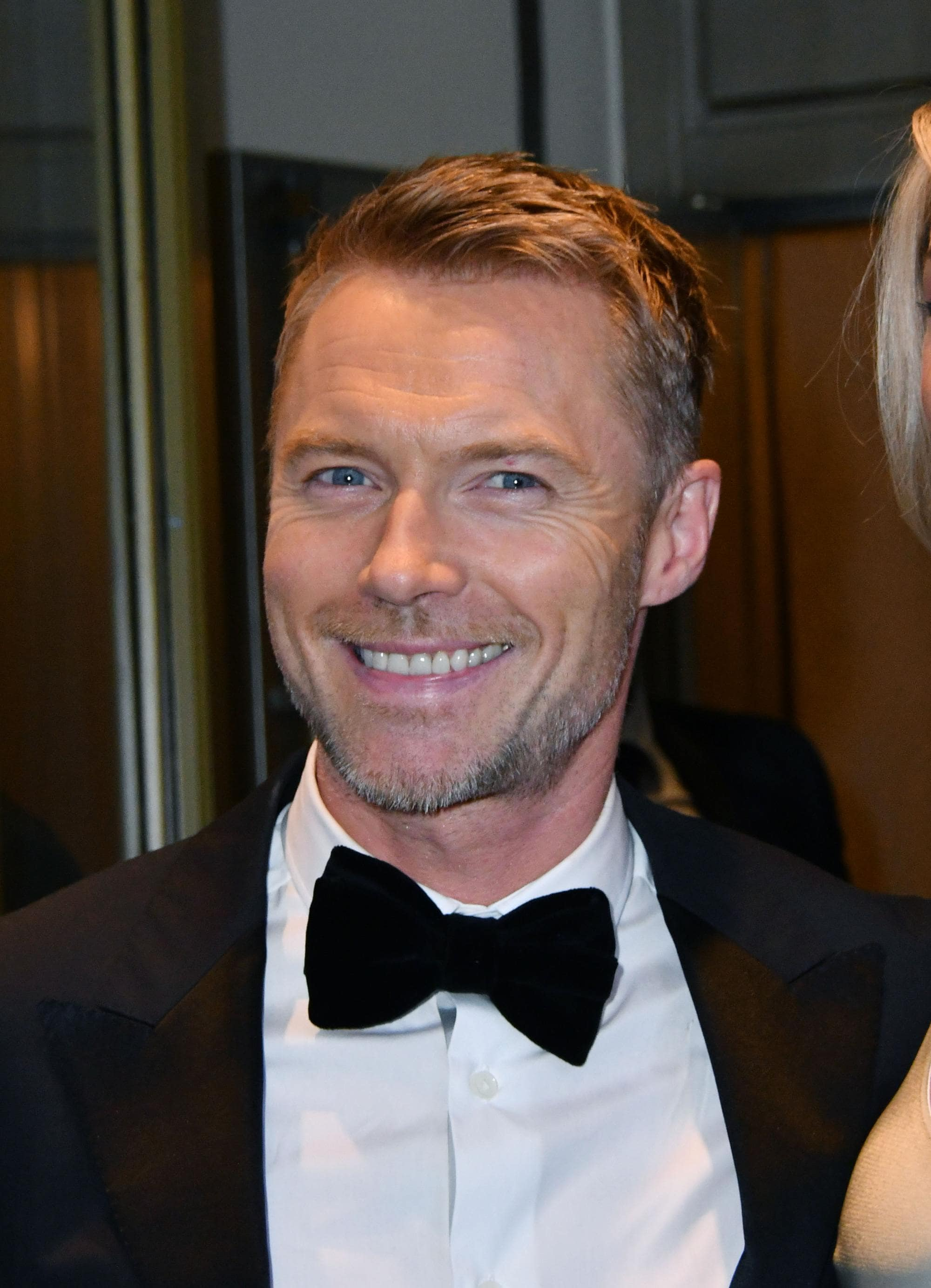 close up shot of ronan keating with side swept hairstyle wearing bow tie and shirt and suit jacket