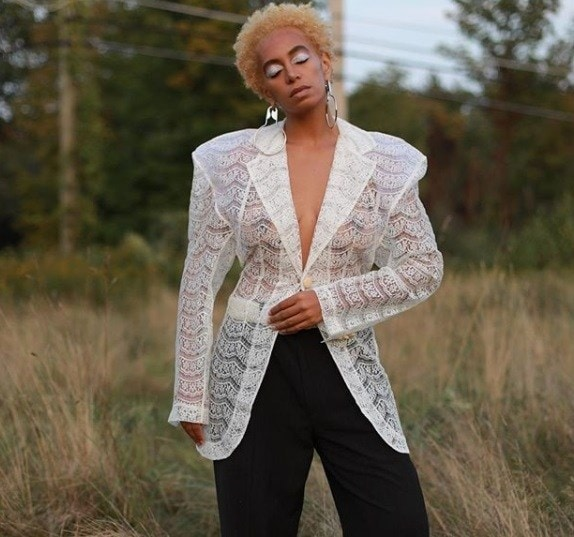 shot of solange knowles with blonde twa on instagram, wearing white and standing in field