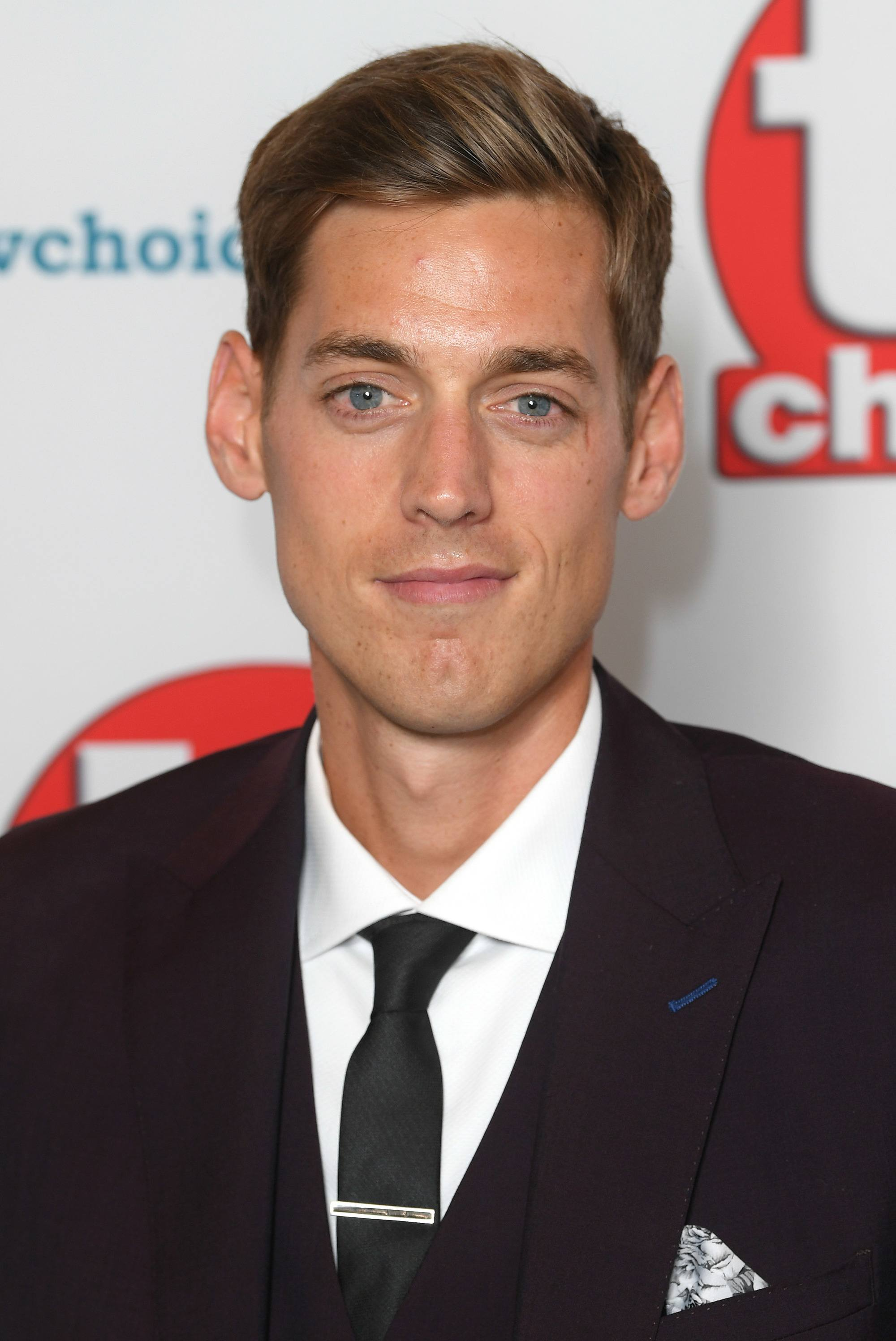 TV Choice Awards: Close up shot of Sam Homewood with dark blonde short hair styled into a swept-back quiff, wearing a black suit jacket with a tie on the red carpet