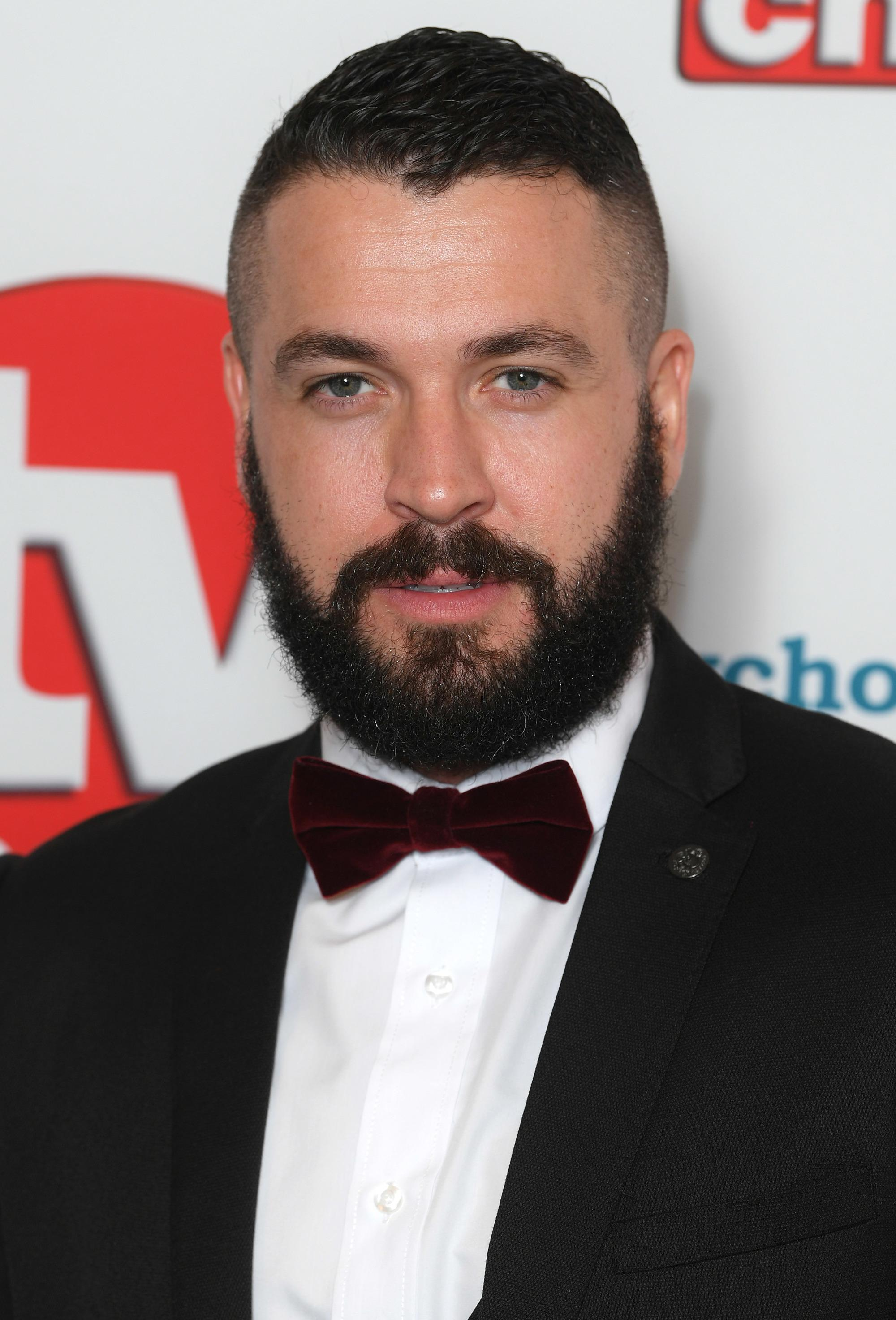 TV Choice Awards: Close up shot of Shayne Ward with a dark brown short crop with a fade and beard, wearing a black suit and bow on the red carpet