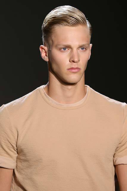 shot of male model on runway with side slick hair swept back wearing nude