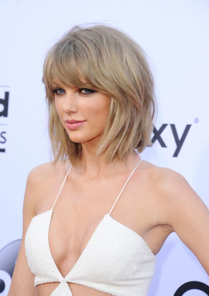 close up shot of taylor swift with shaggy haircut on the red carpet wearing white cutout jumpsuit