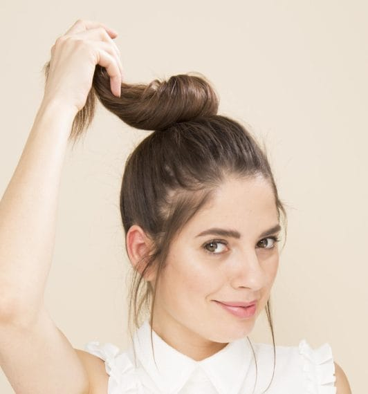 Woman with brunette hair in a ponytail twisting it to make a topknot bun