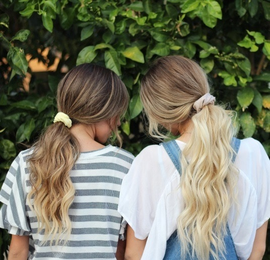 back view of two women with their long hair in ponytails tied with scrunchies
