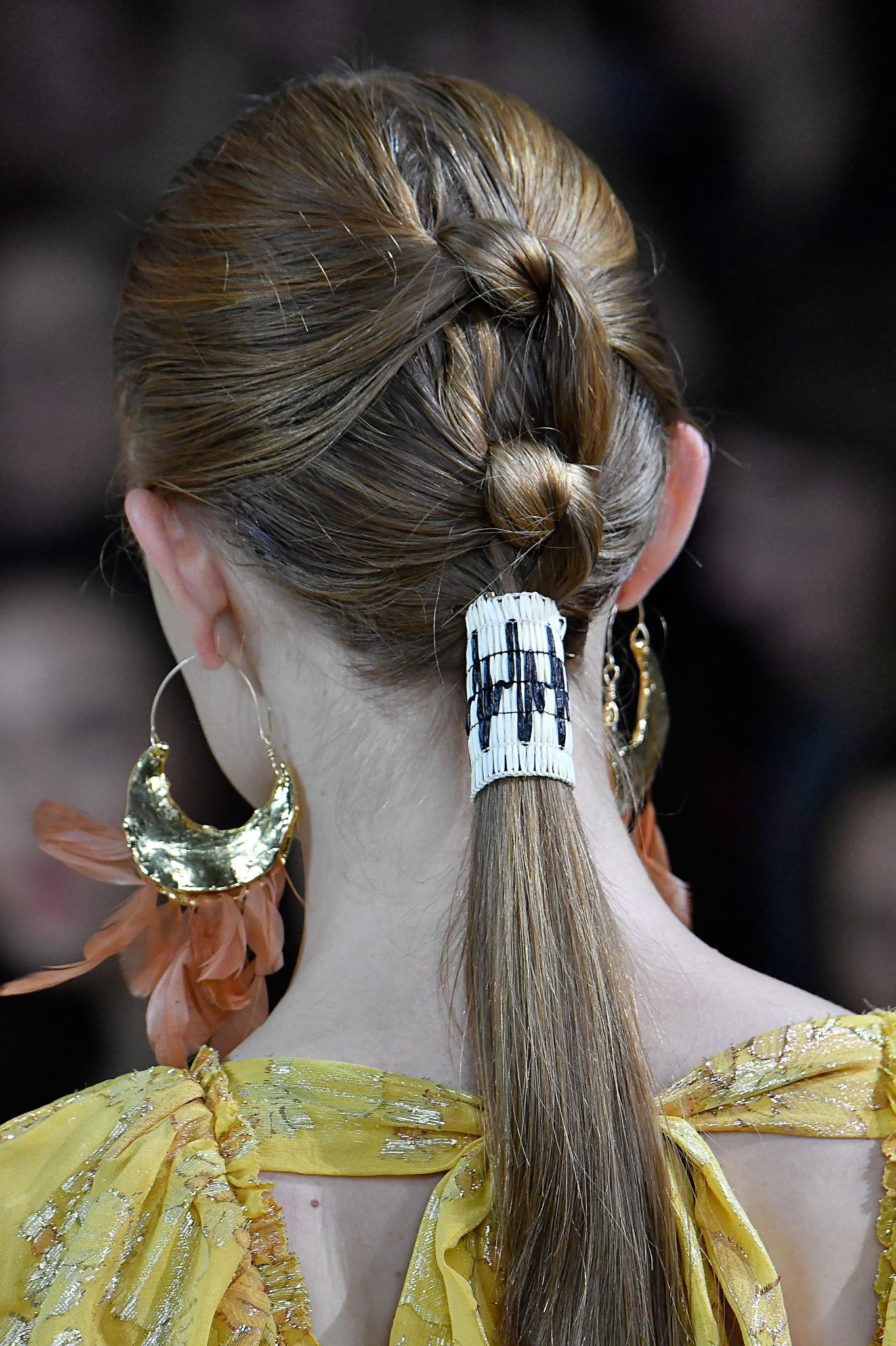 NYFW SS19: Back shot of a model on the Ulla Johnson runway with a knotted light brown medium ponytail,complete with a wrap accessory, wearing big hoop earrings