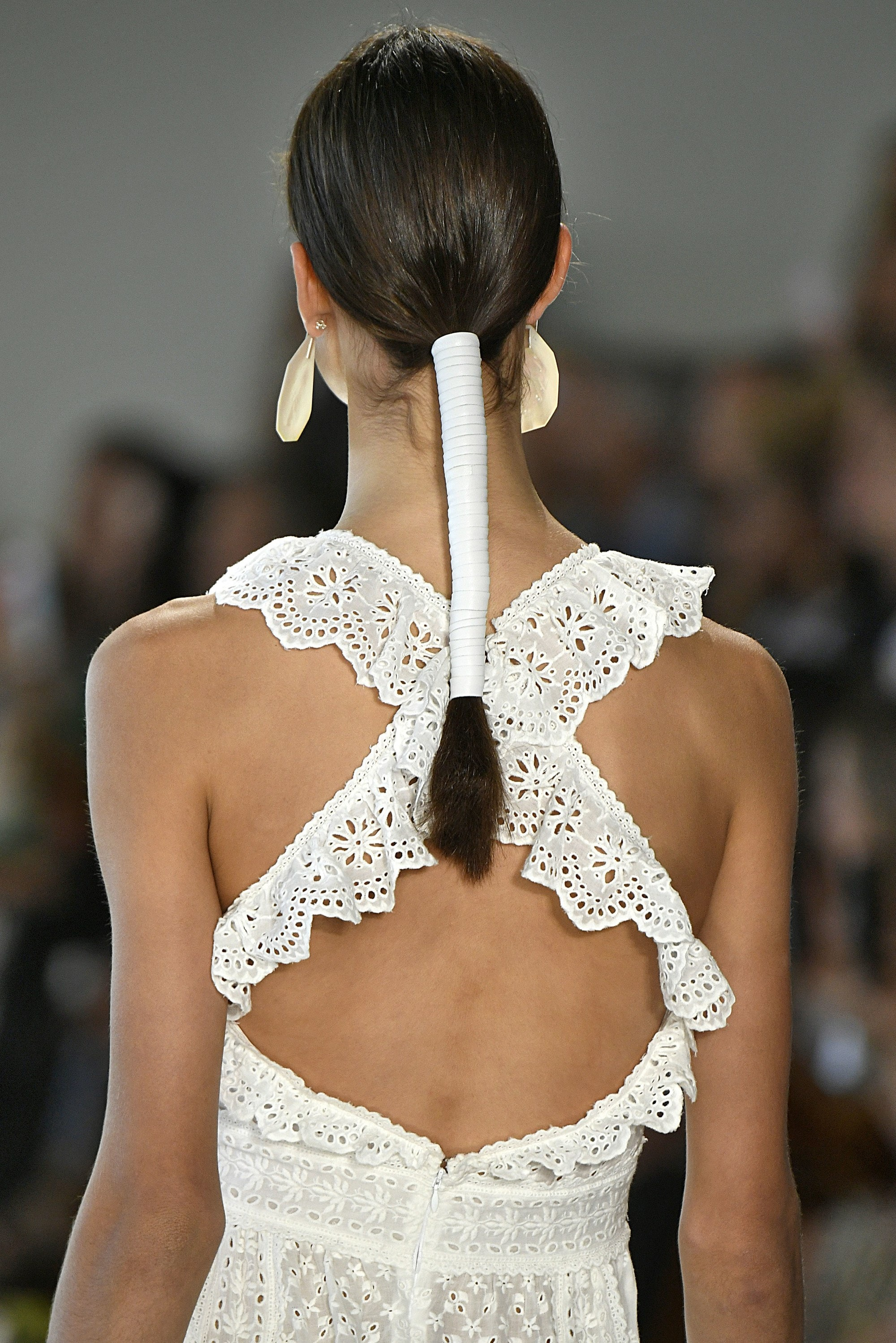 back view of a brunette model with a ponytail wrapped in leather ribbon