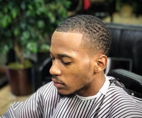 side profile of a man with short wavy hair styled into a bald taper fade