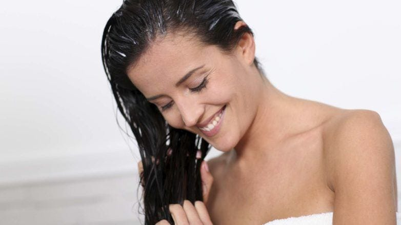 Deep conditioner for dry hair: Model with brown hair applying conditioner to the lengths of her hair, wearing a white towel