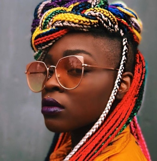 close up shot of woman with colourful box braids with shaved sides