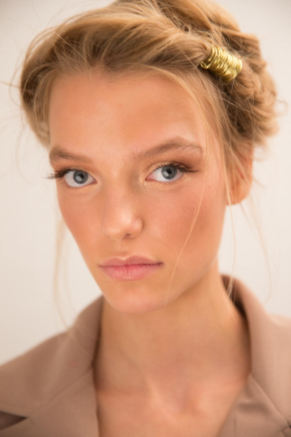 close up shot of model with twist updo with golden hair accessory into it with natural make up