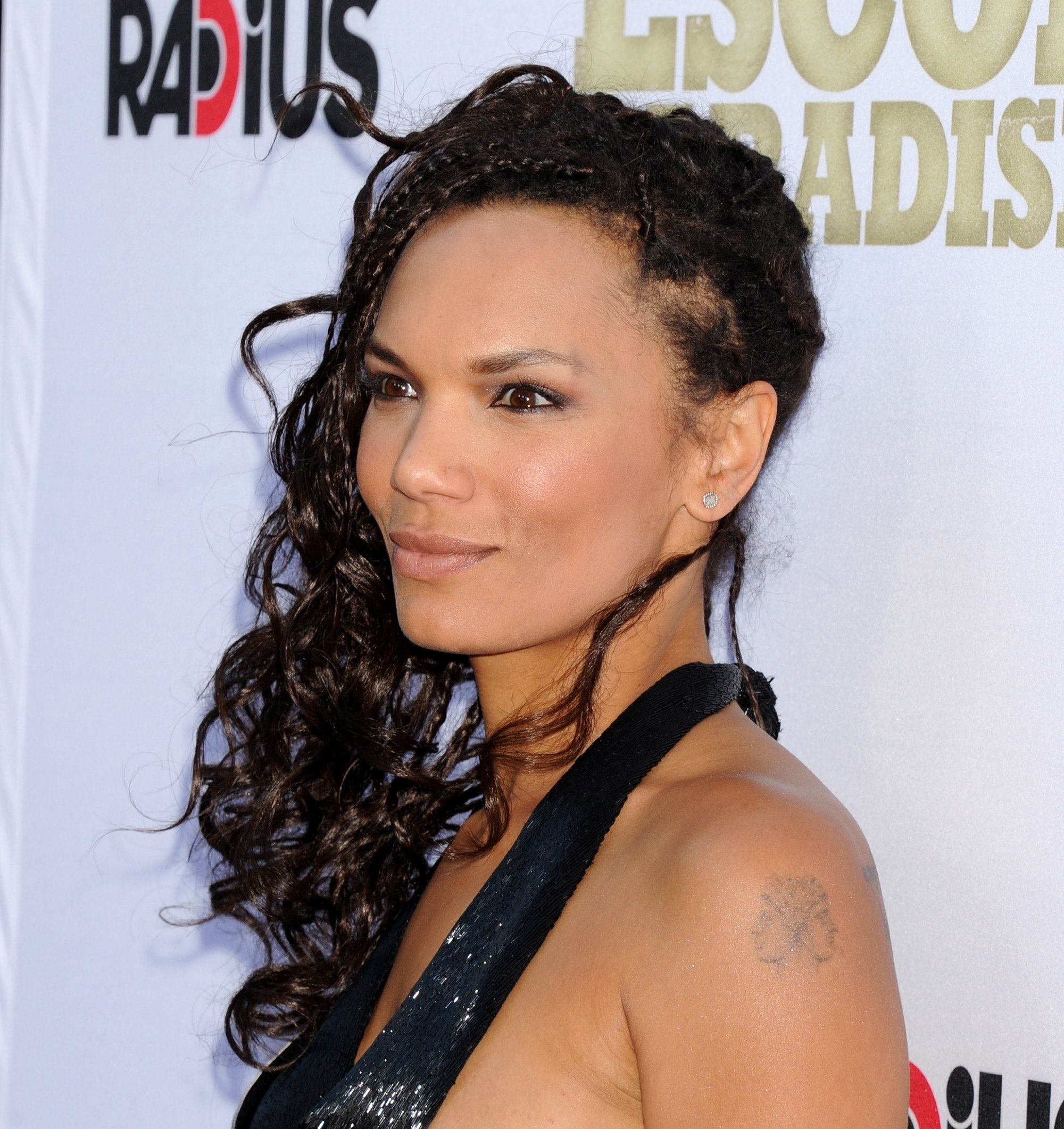 side shot of amber dixon brenner with curly box braids with loose ends on the red carpet, wearing black top