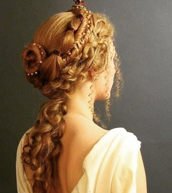 Renaissance hair: Woman with intricate braided golden blonde ponytail hairstyle, wearing a renaissance white dress and posing in studio