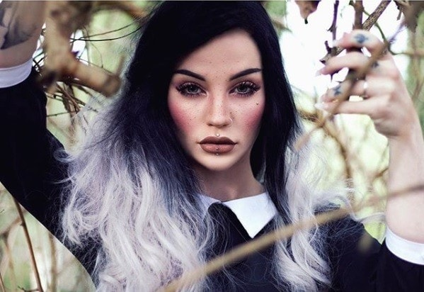 Witch hair: Close-up of a woman with long black to white ombre hair standing outside in the woods wearing a black Wednesday Addams inspired outfit