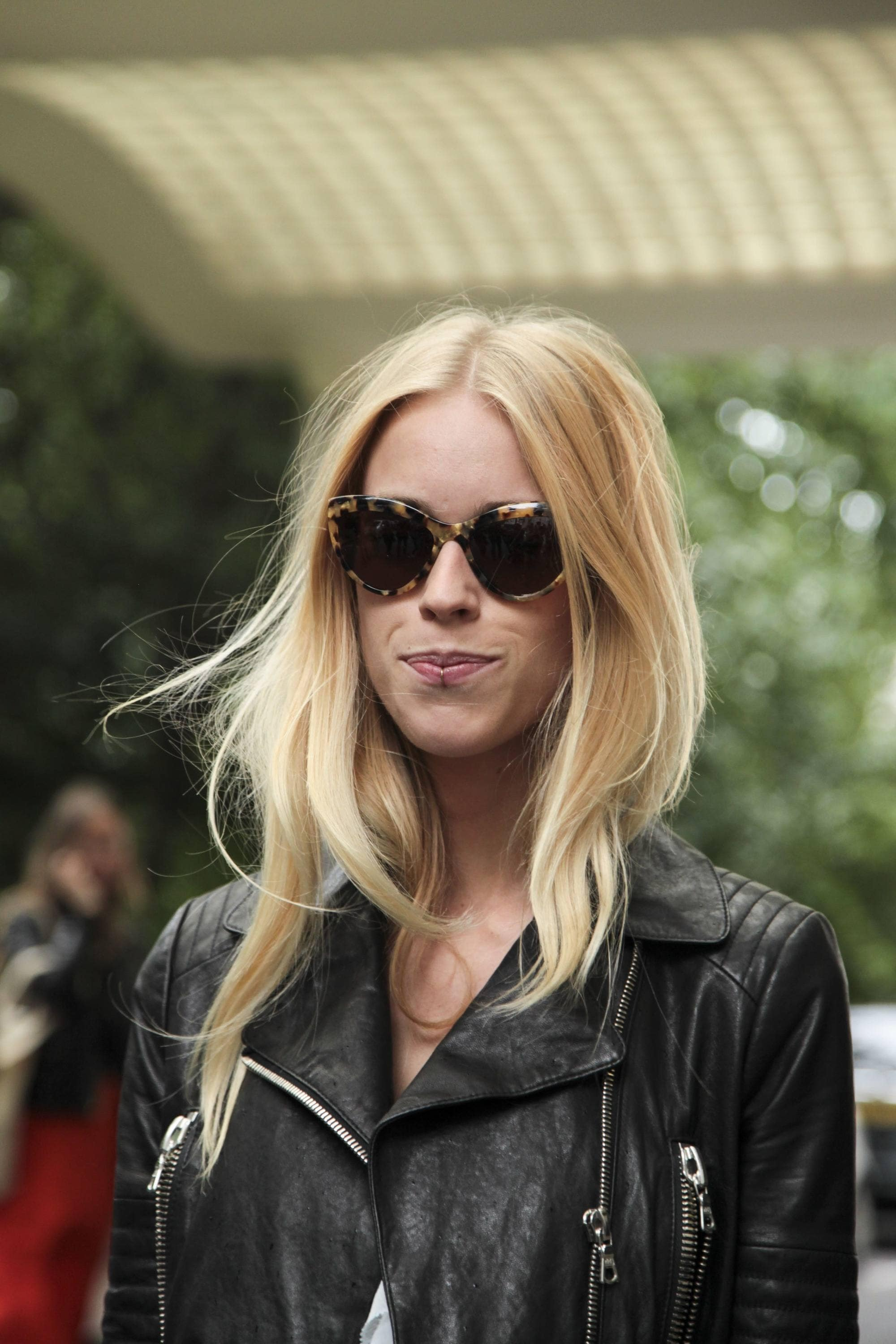 Street style shot of a blonde woman with windswept hair wearing sunglasses