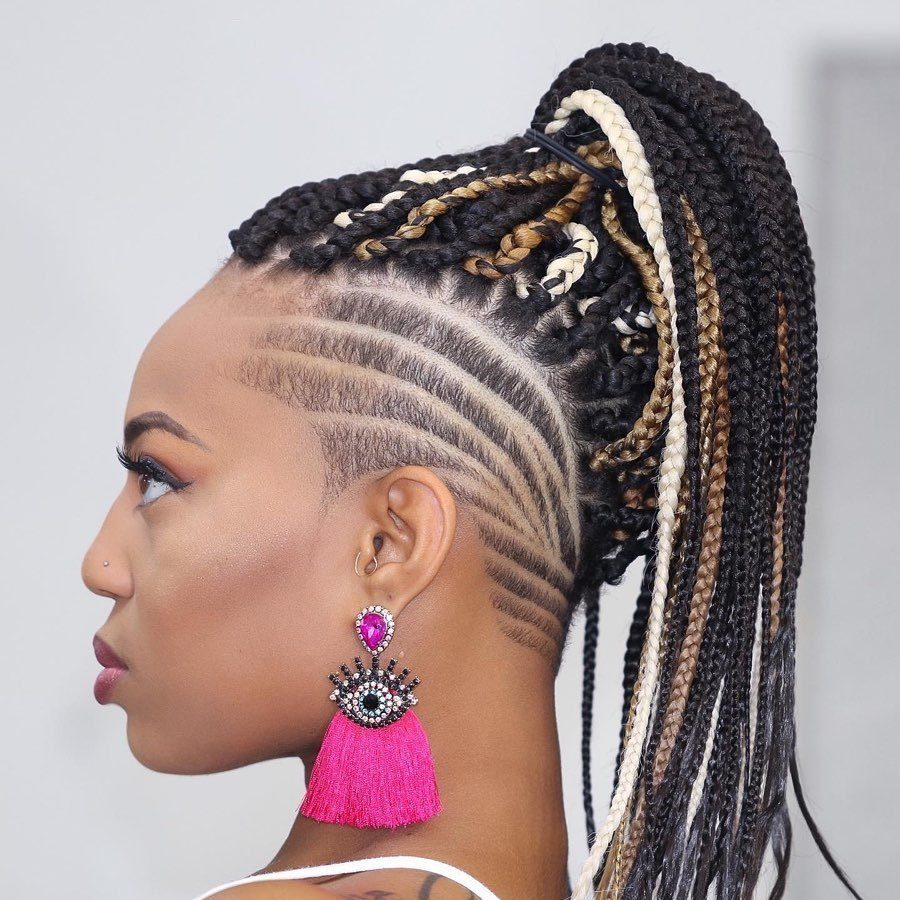 Woman with dark box braids styled into a high ponytail with shaved