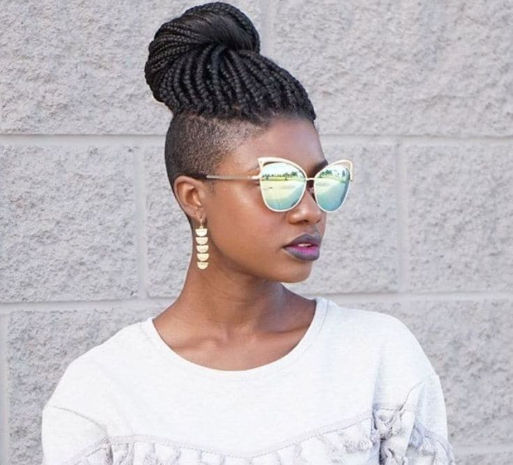 side shot of woman with box braids with shaved sides hairstyle, wearing sunglasses and white jumper