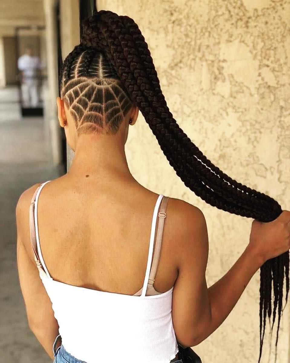 Woman with spider web undercut hairstyle with box braids ponytail