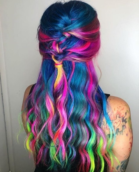 Unicorn hair: Back view of a woman with very long wavy multicoloured hair