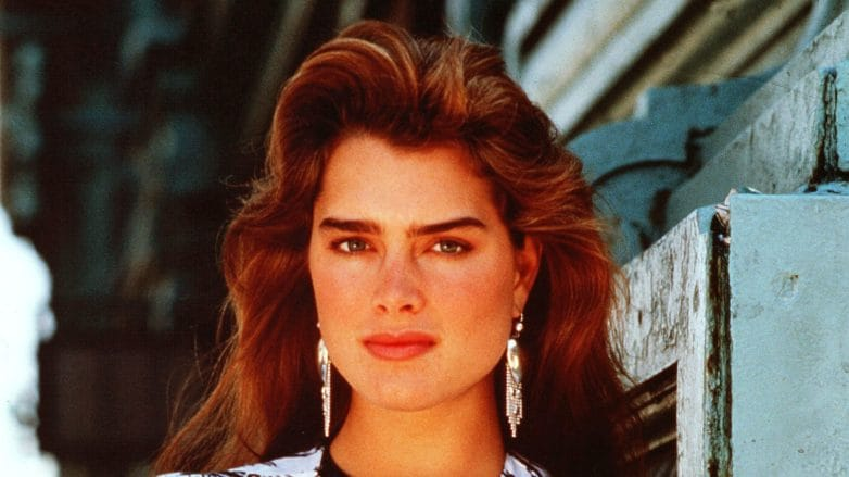 80s hairstyles: Young Brooke Shields with brown big blow dried '80s hair wearing a pattern blazer with her arms crossed